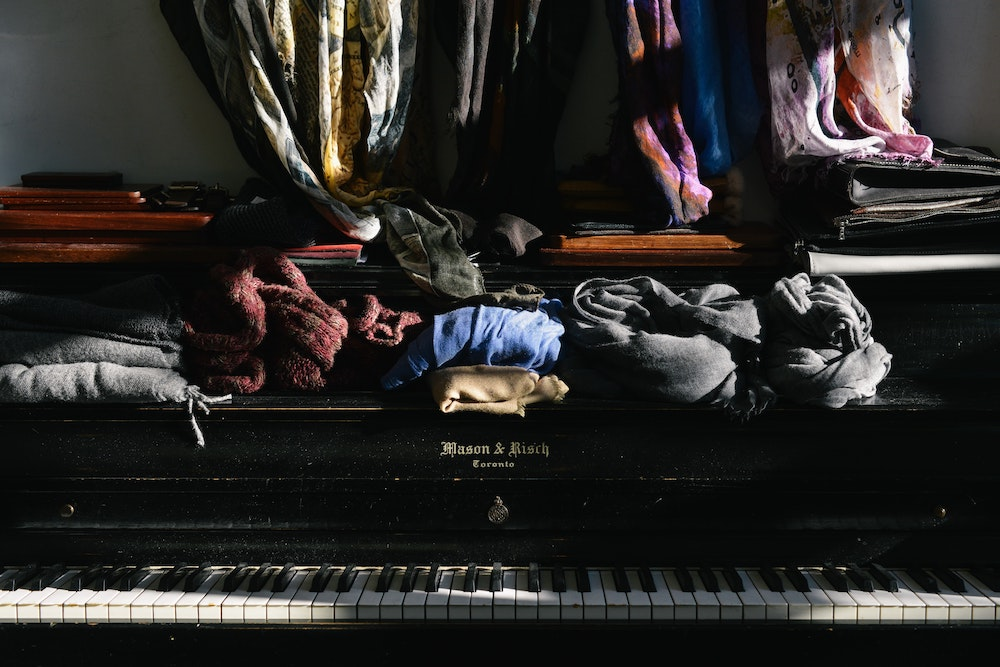 A messy room with piano
